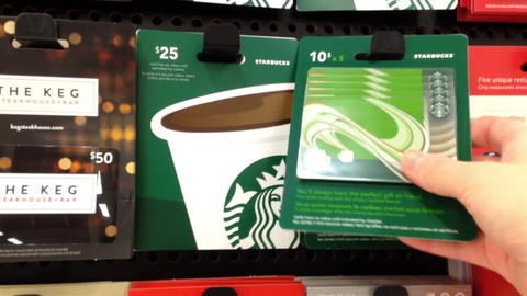Woman picking starbucks gift card to buy Stock Video Footage