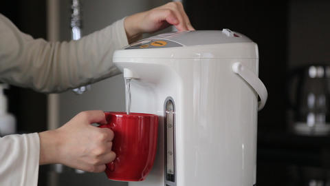 Woman pushing hot water button on electric thermo pot for drinking coffee Footage