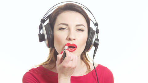 Lovely girl in red listening to the music in big headphones and dancing having f Footage