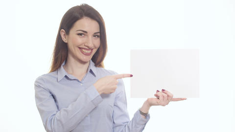 Positive smiling woman in blue shirt pointing at blank piece of paper copy space Footage