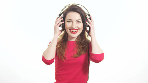 Pretty woman wearing red lipstick listening to the music touching big headphones Footage
