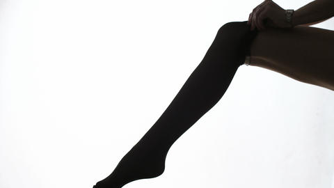 lady puts on stockings in silhouette Footage
