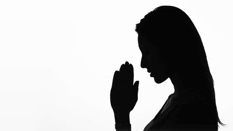 closeup profile of a woman praying in silhouette isolated Footage