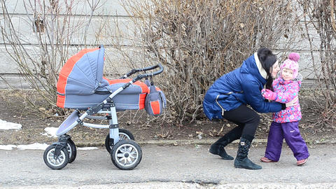 Mother with Daughter Walkin in Park with Newborn Child in Baby Carriage Footage