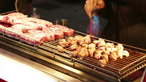 Vendor cooking meat with blowtorch at Lehua Night Market Footage