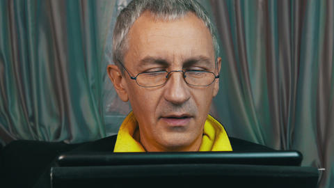 Portrait Smiling Man in Glasses Reading a Tablet Computer Footage