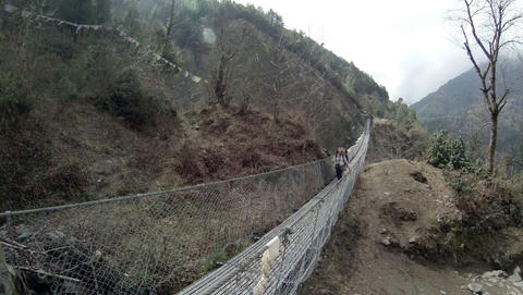 HIMALAYAS, NEPAL - MARCH, 2014: 2.7. Tourists walk on a suspension bridge in the Live Action