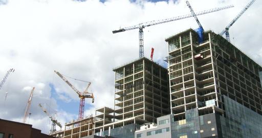 Cranes on construction site around skyscrapers Footage