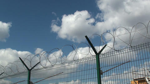 Secured area with a tower, a fence and barbed wire Footage