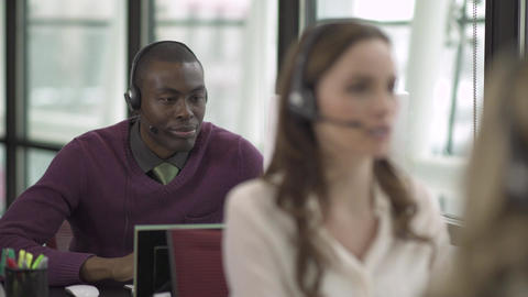 A Black Man Works in a Attractive Modern Call Center (2 of 4) Footage