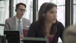 A Caucasian Man in a Suit Works in a Attractive Modern Call Center (4 of 4) GIF