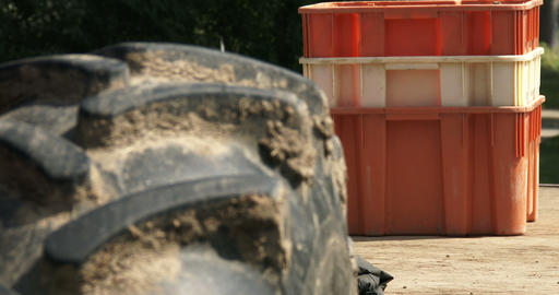 Close up of tractor's tyre with crates behind Footage