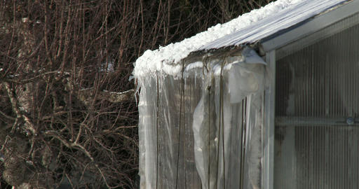 Snow melting on the roof of a small greenhouse Footage