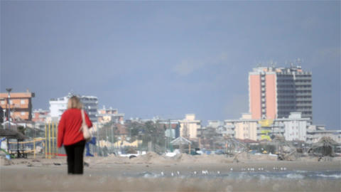 Woman in red jacket walking on the beach 2 Footage