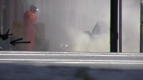 Worker spread dust on the street with a compressor 01 Footage