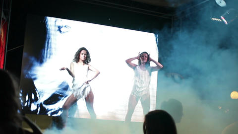 Two sexy strip dancers on the stage of summer nightclub in smoke (with crowd) Live Action