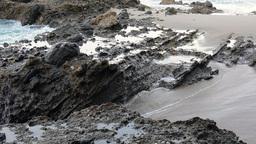 Pan of rushing seawater over shoreline reef Footage