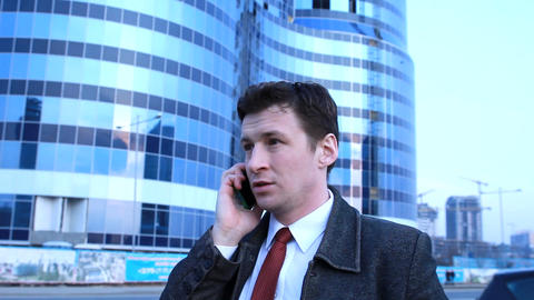 Male Businessman Talking On The Phone Near A Big Building stock footage