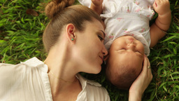 Mother Kissing Little Baby Daughter Laying Closed On Grass Footage