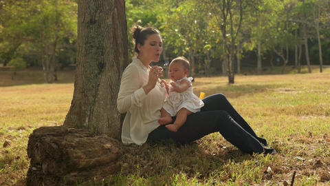Mother Playing Soap Bobbles With Little Baby Daughter In Park On Grass Footage