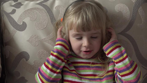 Little Girl in Headphones Listening to Music.Moving. Head shake. 4k Ultra HD Footage