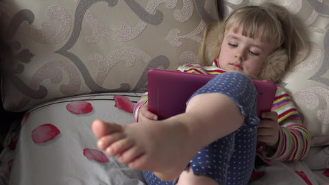 Smart Little Girl Using Tablet Computer while Sitting on Couch. 4k Ultra HD Footage