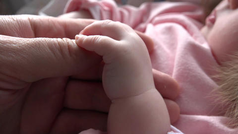 Father's and Baby's Hands. Closeup. 4k Ultra HD Footage