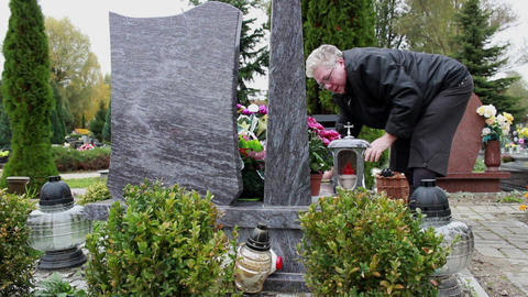 Middle-aged woman cleaning tombstone 2 Footage