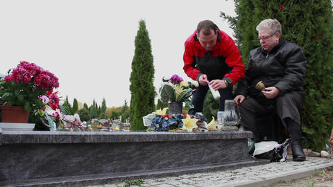 Son and his mother lights a candle at the grave of his/her father/husband Footage