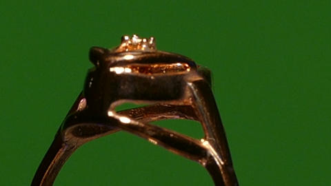 BIG jewelry ring rotates on a green background , 50p Footage