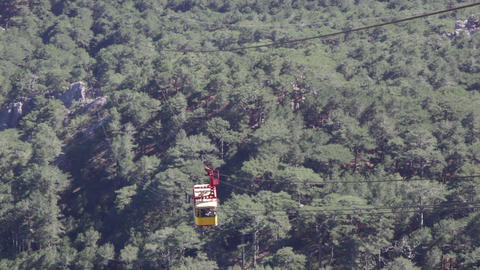 Yellow booth of a ropeway on Ai Petri rises uphill over trees Footage