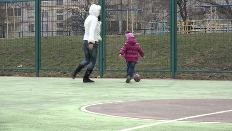Girl Playing Football With Mother On Sport Playground.. 4K UltraHD, UHD stock footage