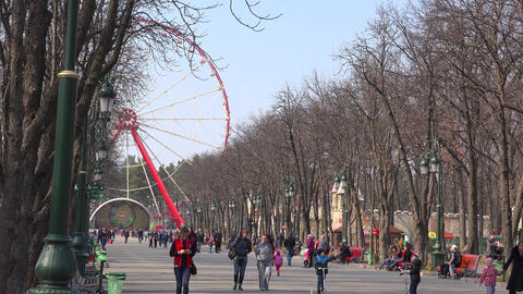 KHARKOV - APRIL 21: Gorky Park City, people walking in alley with ferris wheel,  Footage