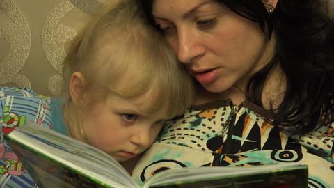 Young Mother with her Little Daughter Reading the Book Together.. 4K UltraHD, UH Footage
