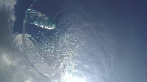 Plastic Bottle Thrown into a Quiet Pool of Clear Fresh Water Footage