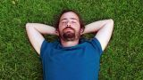 Young guy sleeps on grass Footage