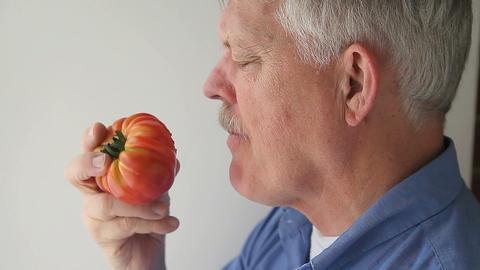senior eats tomato Footage