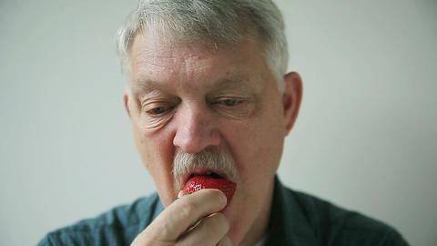 senior man eating strawberry Footage
