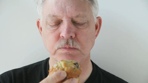 older man eating blueberry muffin Footage