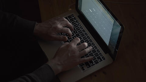 Man typing on a laptop late at night. Filmed in 4K UHD Footage