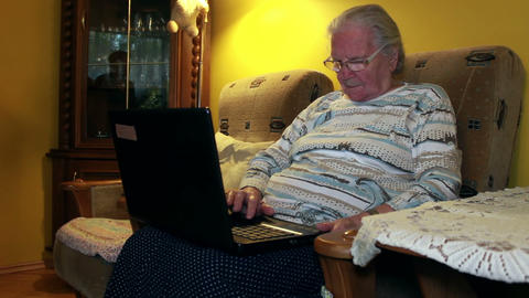 Elderly woman tries to use laptop computer Footage