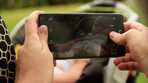 Mother Shoots Picture To Baby In Pushchair With Phone stock footage