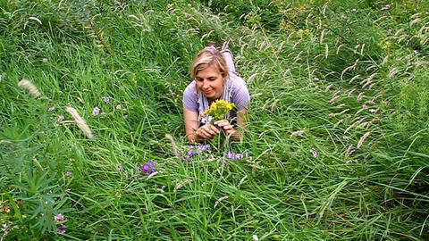 Happy woman lying on green grass in the meadow Footage