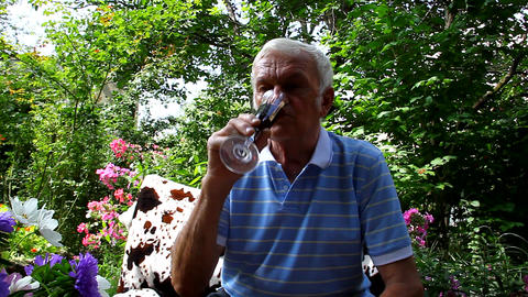 An elderly man tries and drinking wine in the glass outdoors Footage