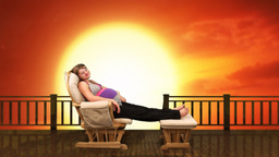 Pregnant woman on rocking chair at sunset Stock Video Footage
