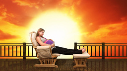 Pregnant woman on rocking chair at sunset Footage