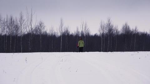Girl walking in winter field. 4K Footage