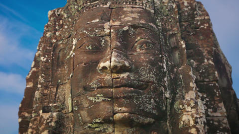 Giant stone face carved from stone at Bayon Temple. Cambodia Live Action