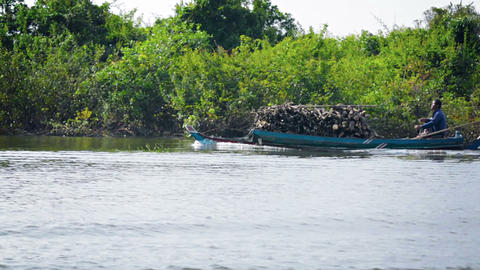 TONLE SAP LAKE. CAMBODIA - CIRCA DEC 2013: Cambodian man carrying a cargo of cut Footage