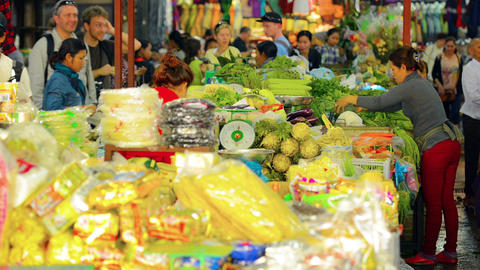 SIEM REAP. CAMBODIA - CIRCA DEC 2013: Foreign tourists and locals shop the veget Footage